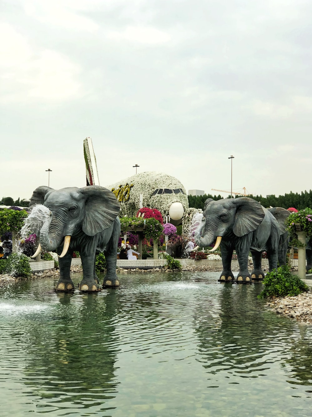 two gray elephants statue on pond during daytime