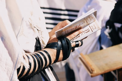 shallow focus photo of person holding book bar mitzvah zoom background