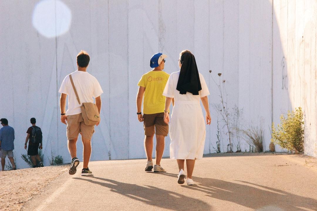 Nun and seminarians walking along the wall