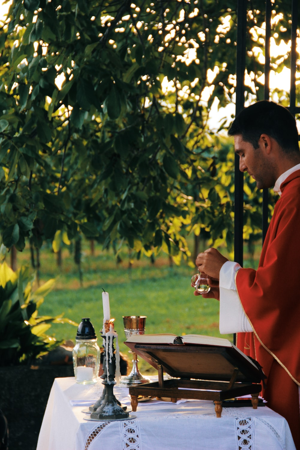 priest holding bottle in front of altar
