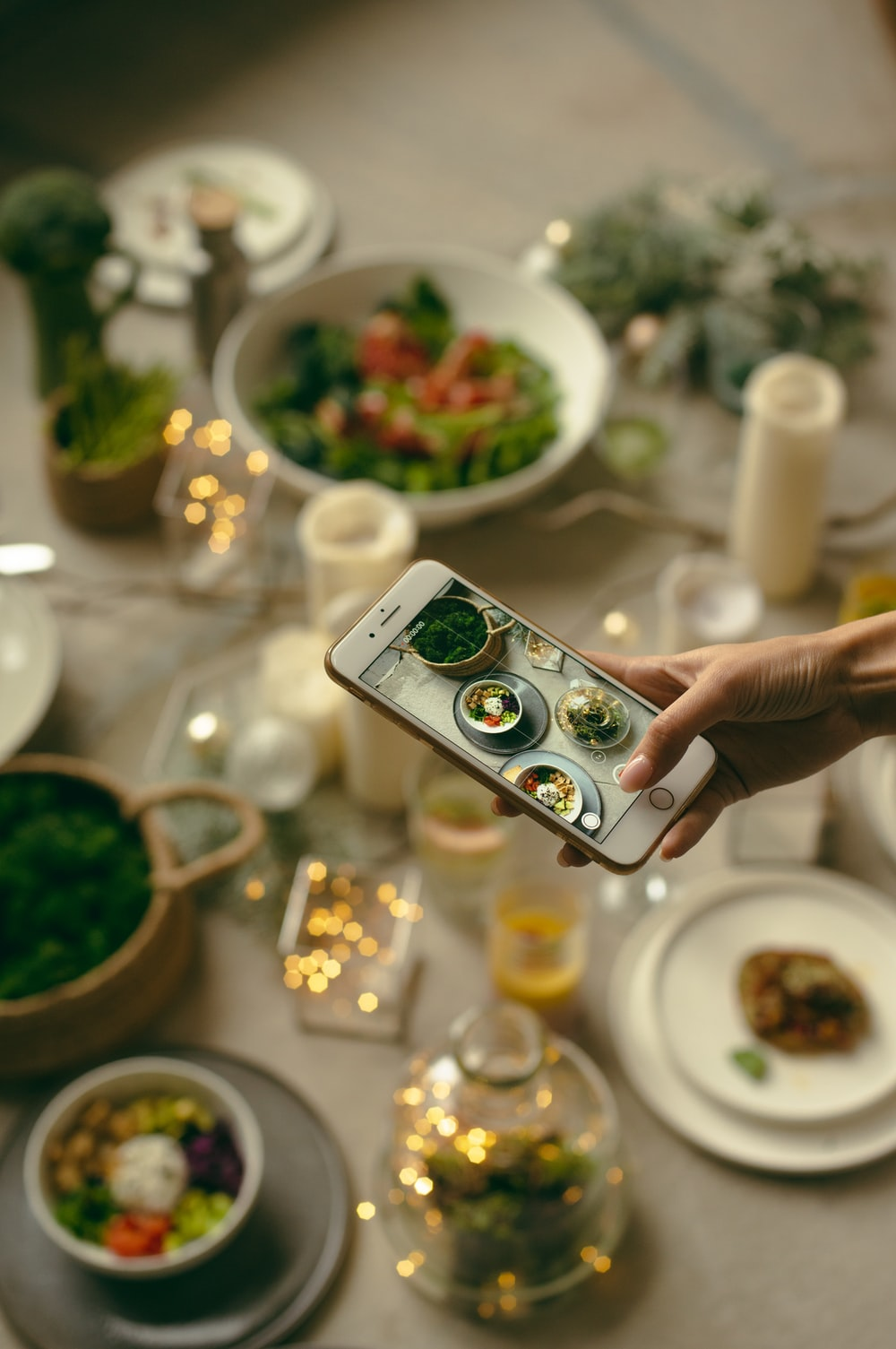 person taking picture of variety of food using phone