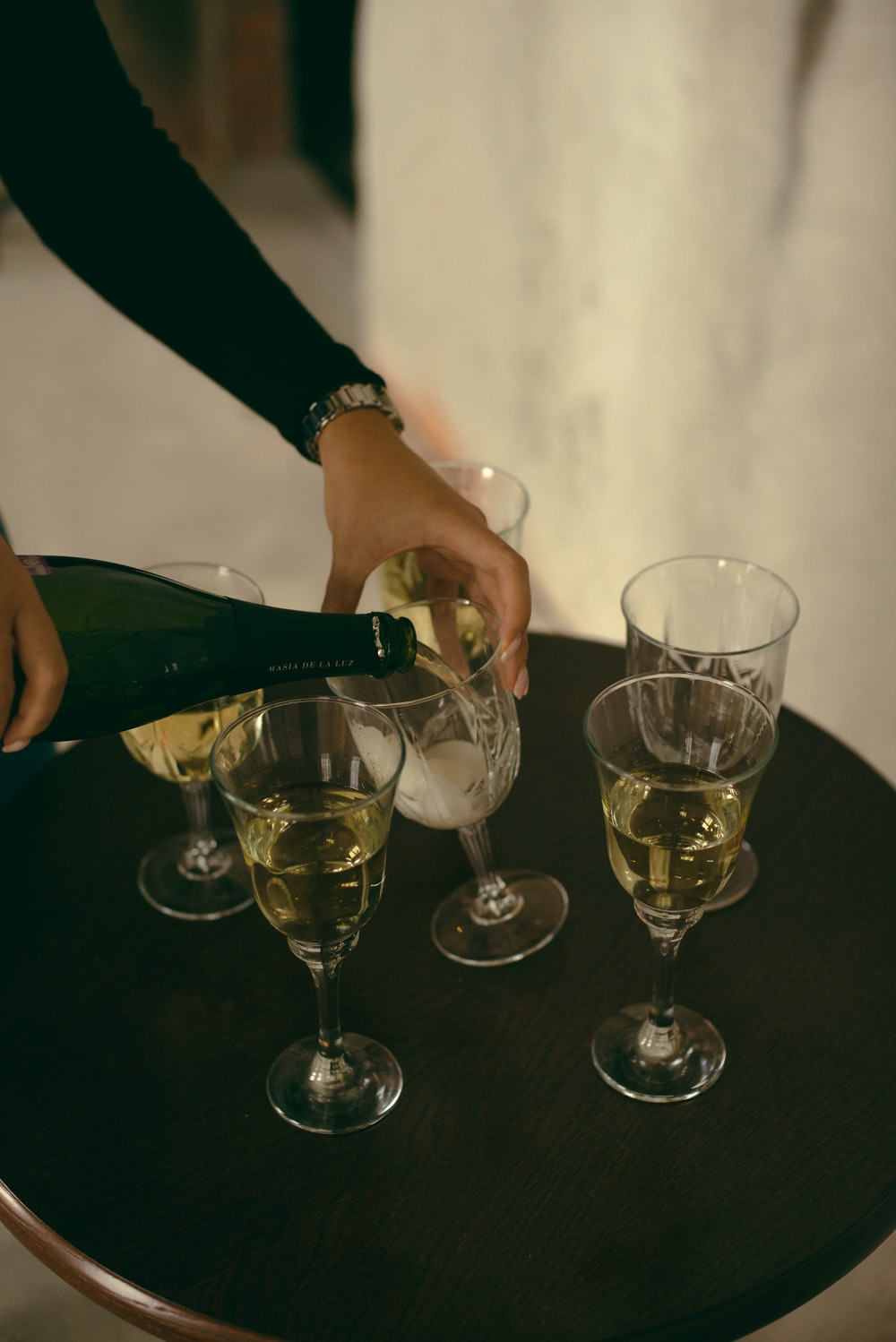 shallow focus photo of clear footed wine glasses on black table