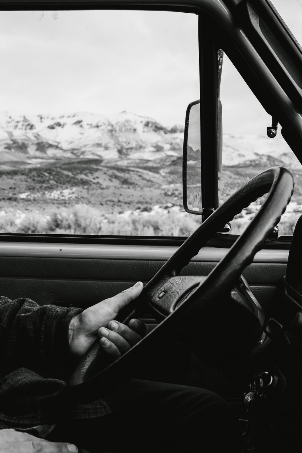 grayscale photo of man driving vehicle