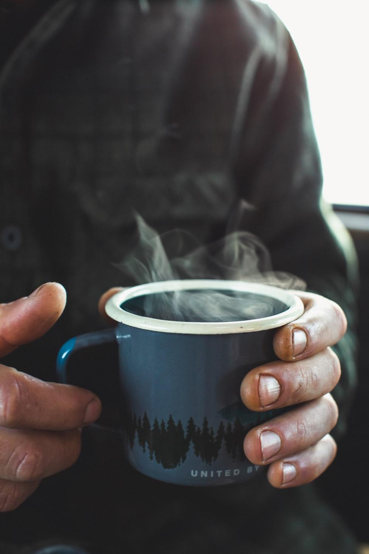 shallow focus photo of person holding blue ceramic mug