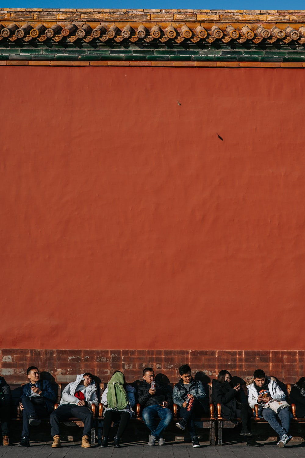 man sitting beside the wall