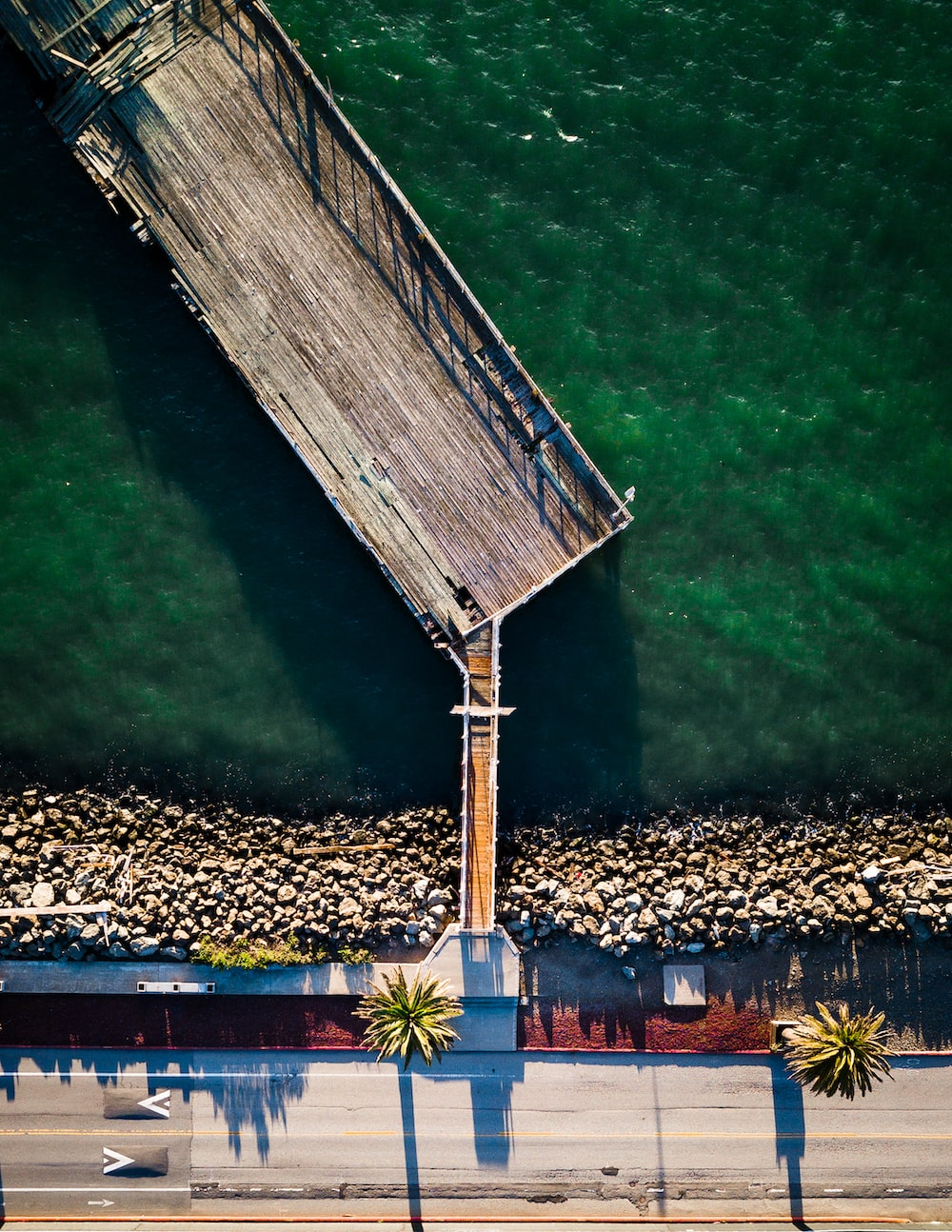 roadway beside brown wooden dock in aerial photography
