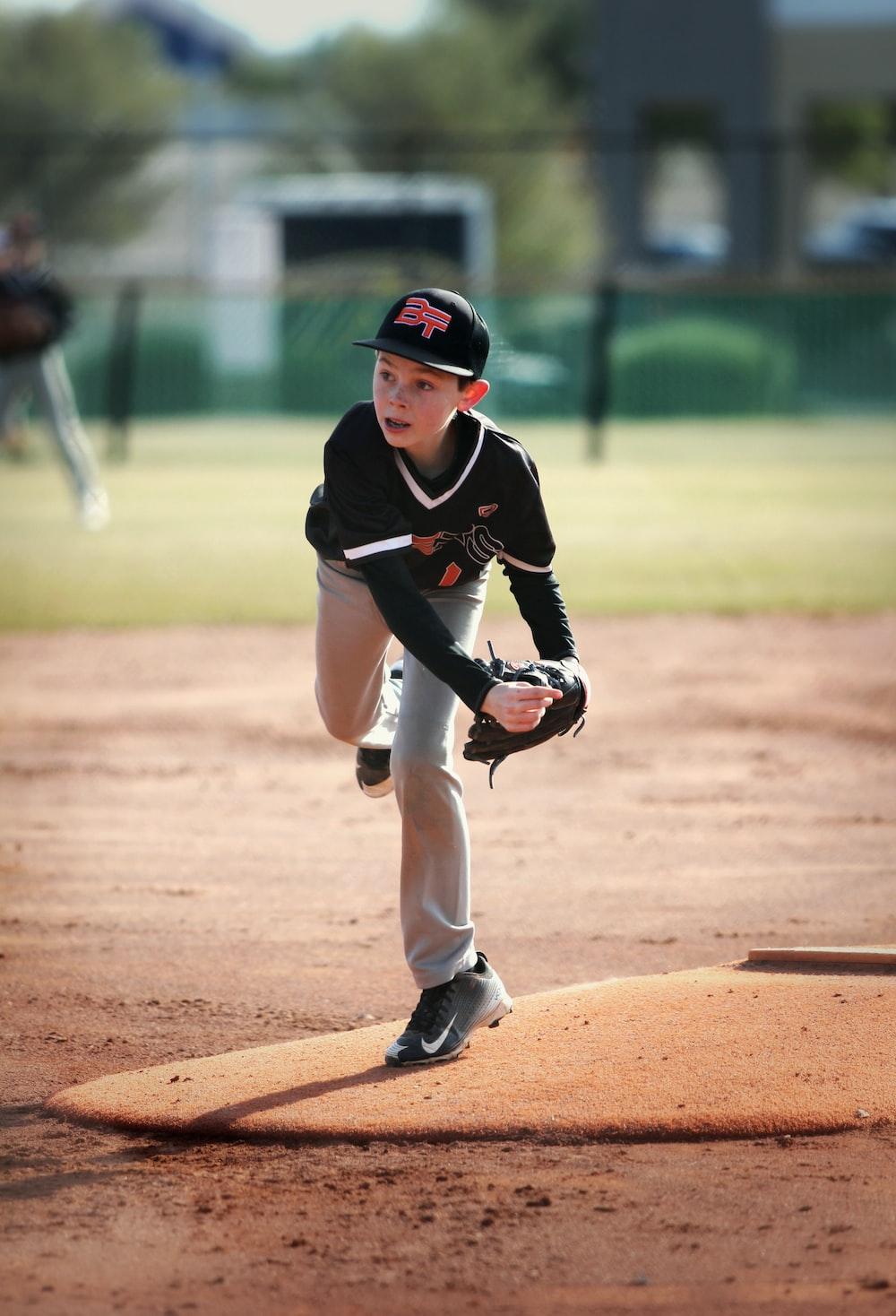 shallow focus photo of boy wearing black baseball jersey