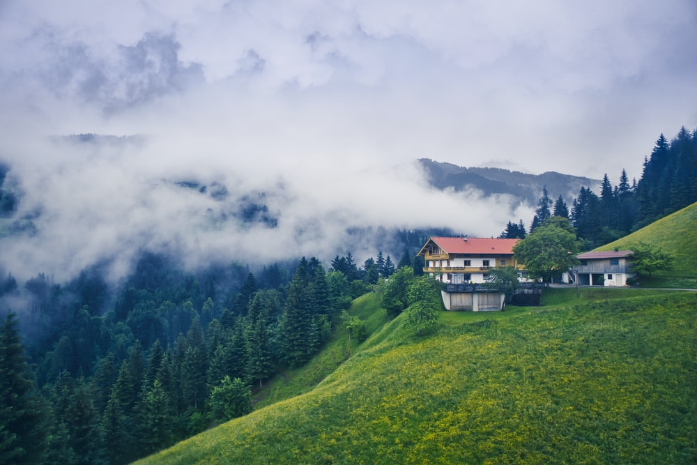 landscape photography of white and red 3-storey house beside green mountain ranges under white fogs during daytime