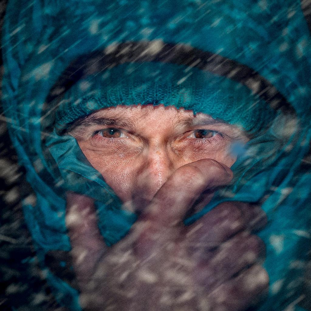 man in teal snow jacket