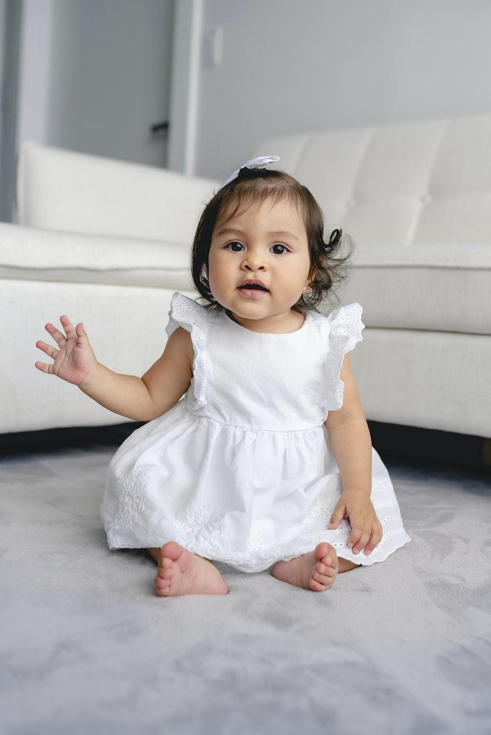 toddler wearing white dress sitting beside white sofa