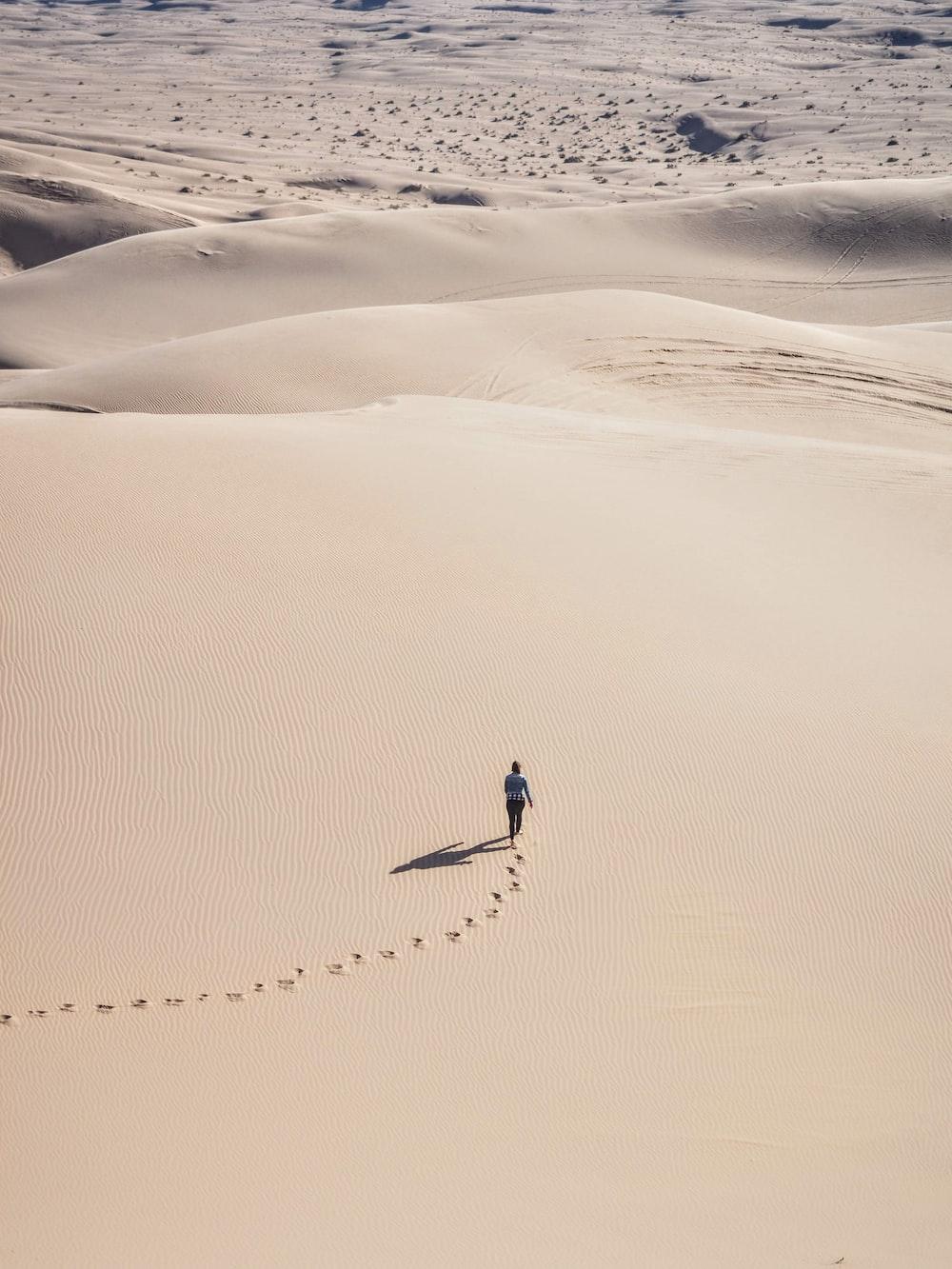 person walking on desert sand during daytime