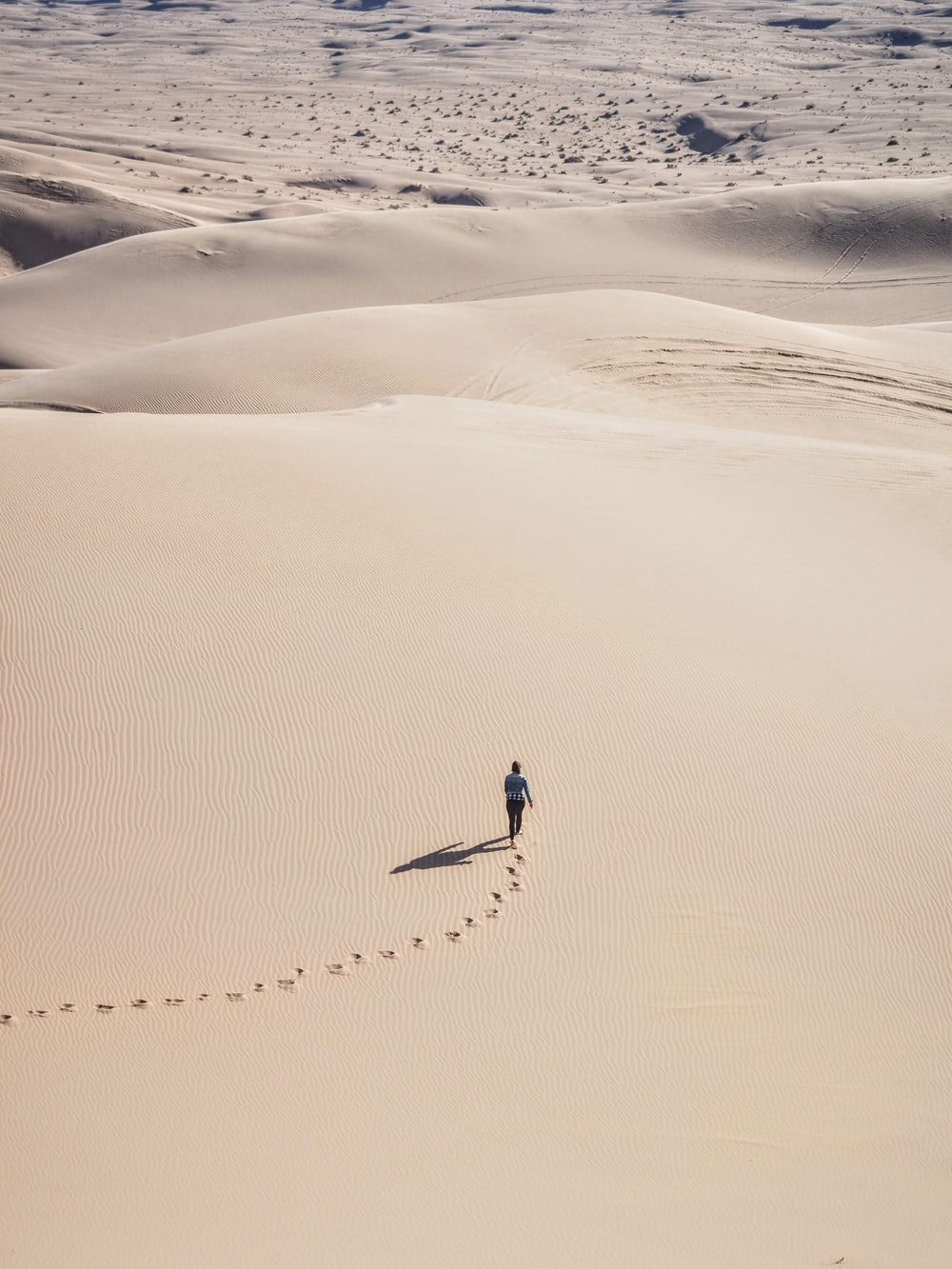 person walking on desert sand during daytime