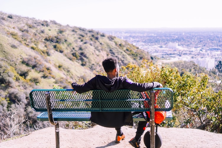 A photo of a man on a bench, looking out over a canyon, shot from behind.