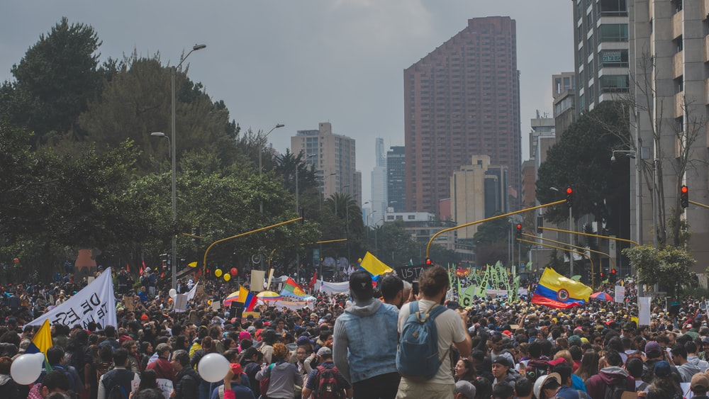 people protesting near buildings during daytime