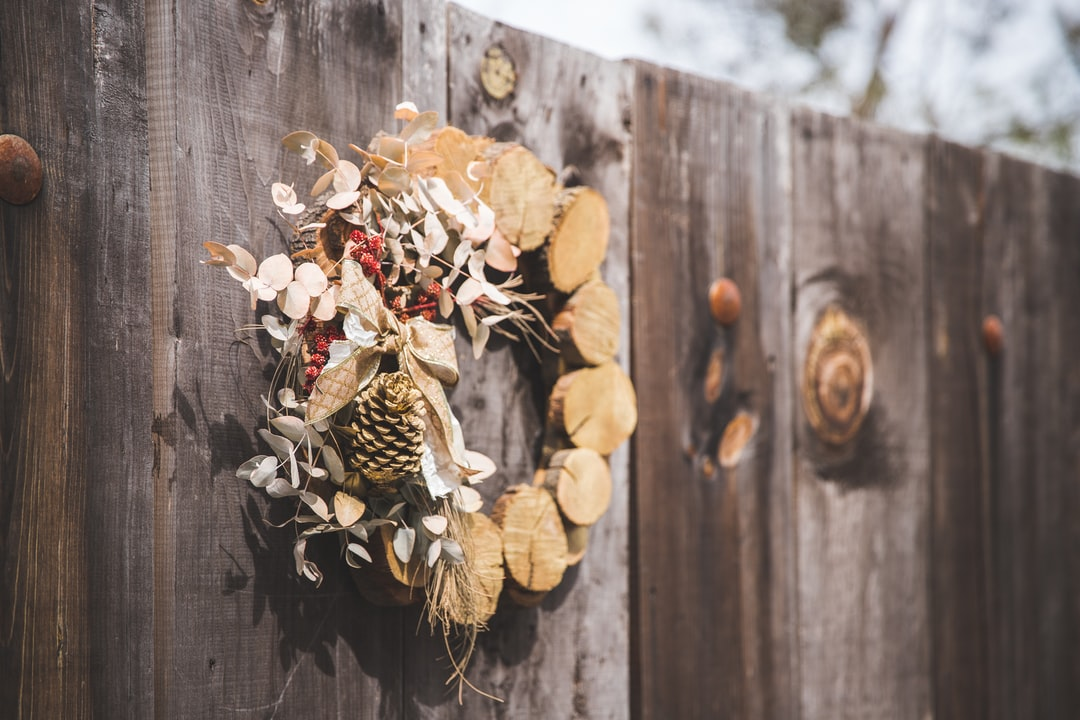 Brown Wreath With Pine Cone Hanging On Wooden Fence - unsplash