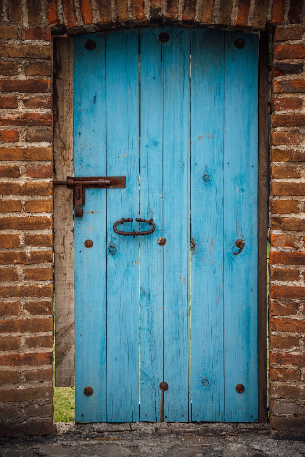 blue wood plank gate and brick wall