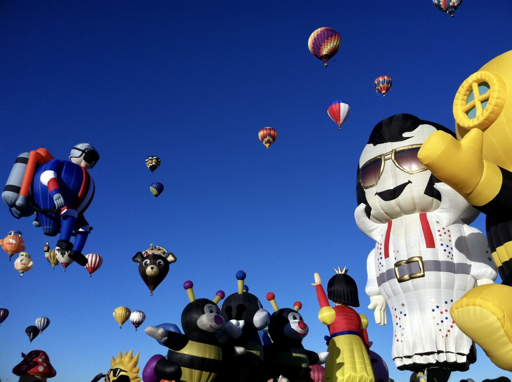 inflatables characters and hot air balloons under blue sky