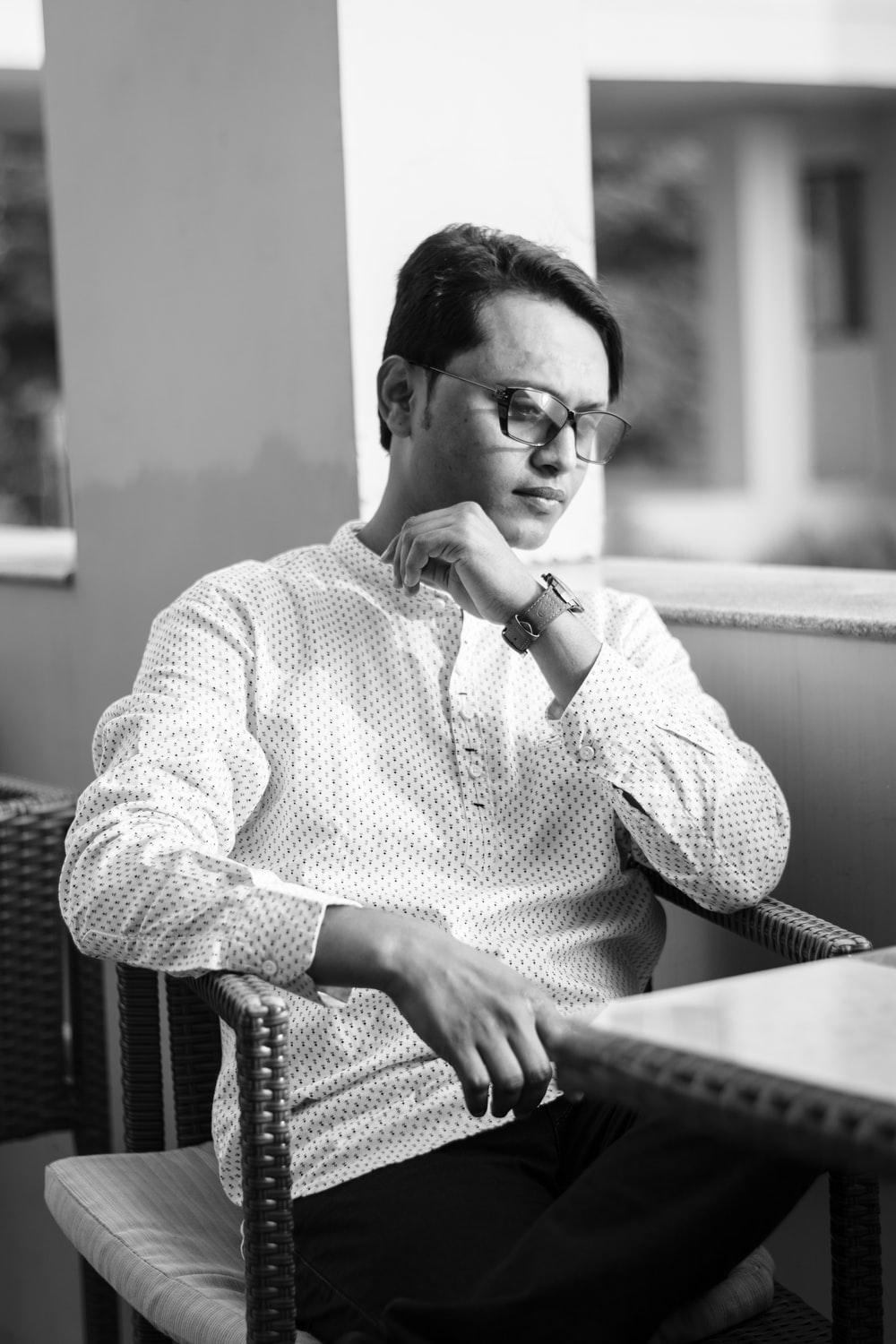 grayscale photography of man wearing long-sleeved shirt sitting with crossed legs near table