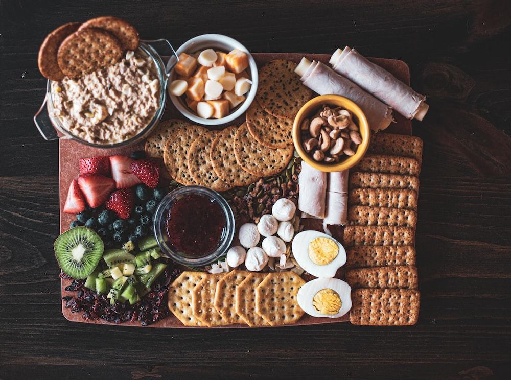 crackers near sliced strawberry, kiwi, and blueberry fruits beside sliced boiled eggs