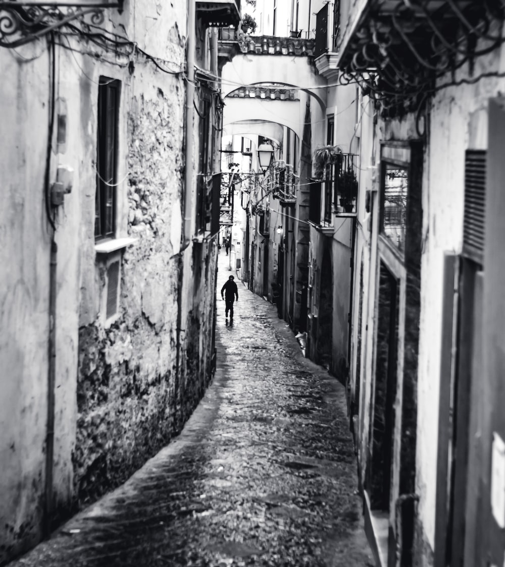 grayscale photography of man walking on pathway surrounded by building