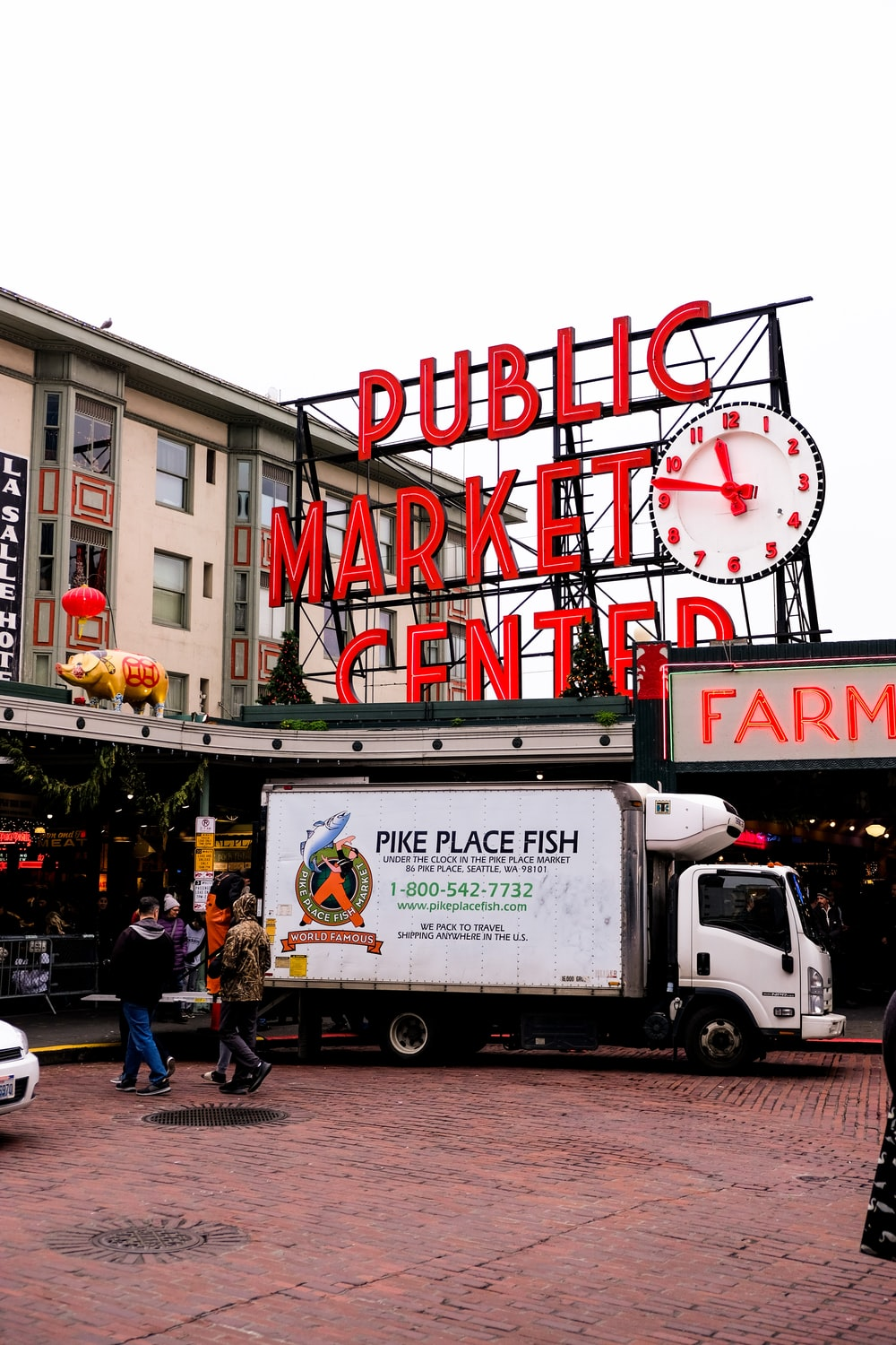 people and Pike Place Fish luton truck parked beside Public Market Center during day