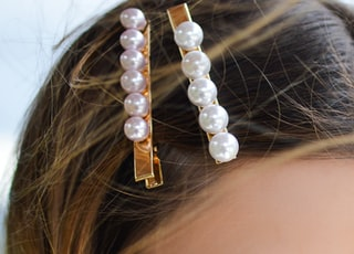 woman with two beaded clips clipped on her hair looking downwards
