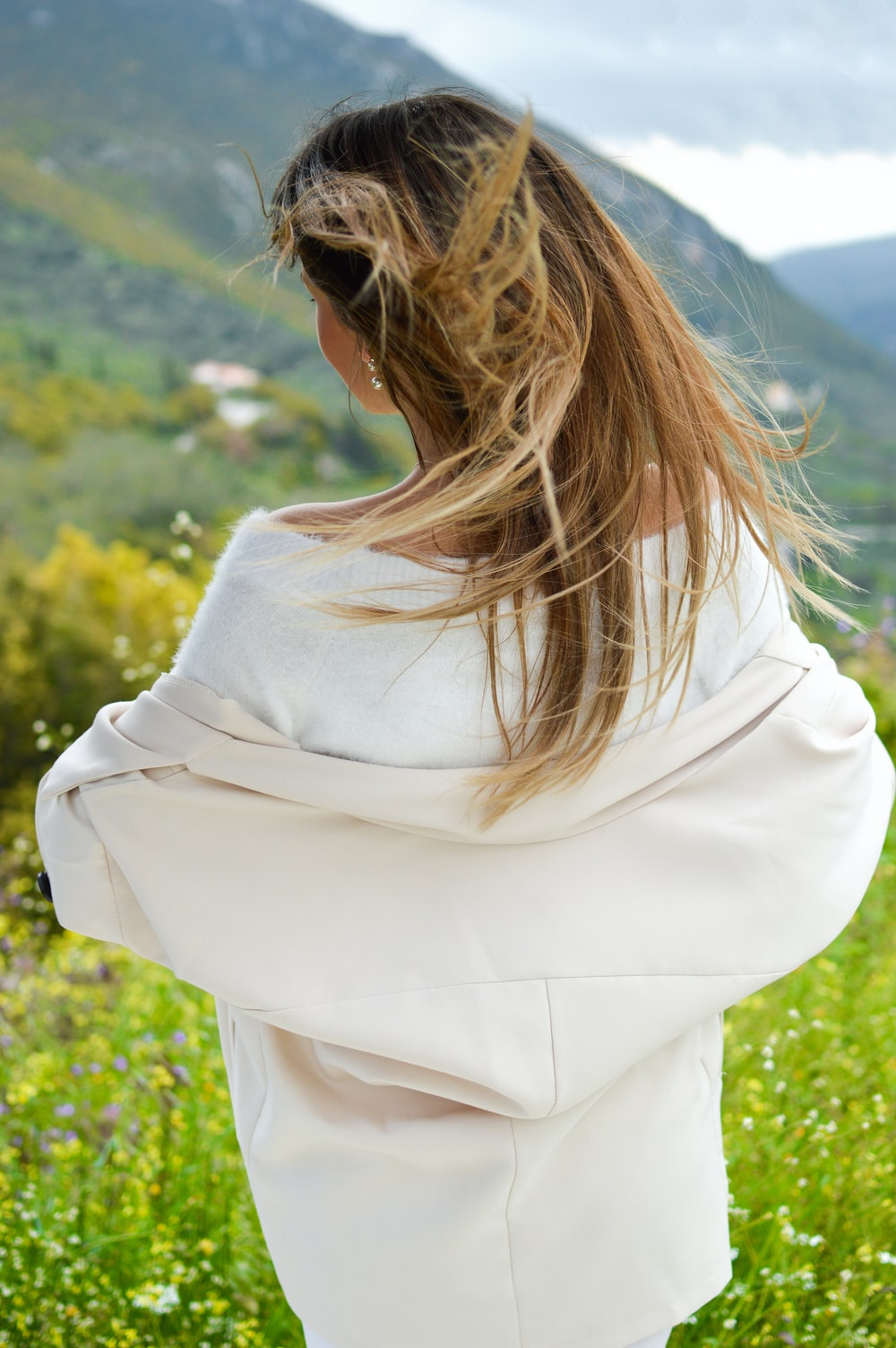 woman wearing white top facing the field during day
