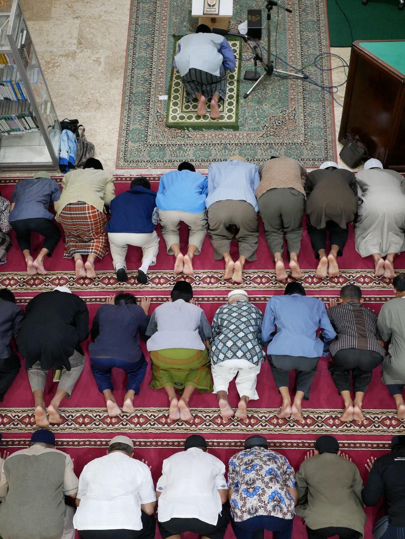 people kneeling on red carpet in church