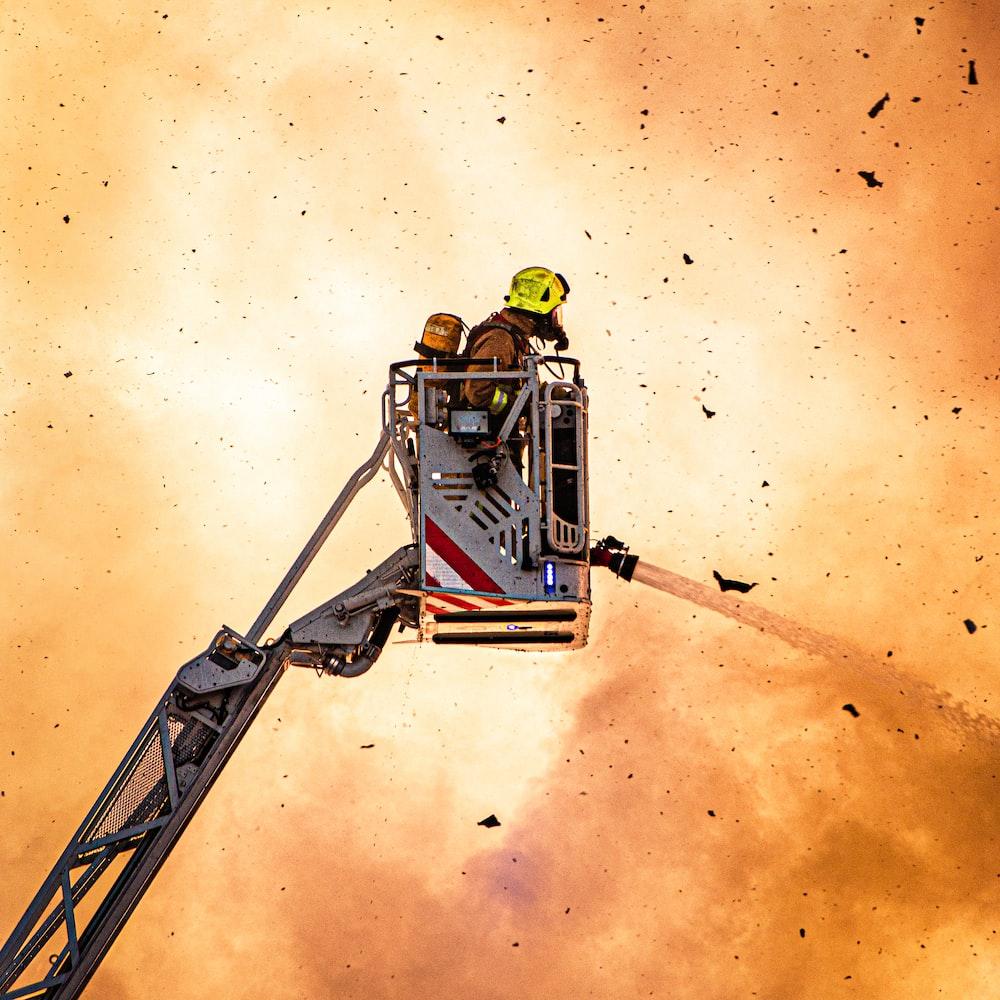 firefighter using fire hose on crane