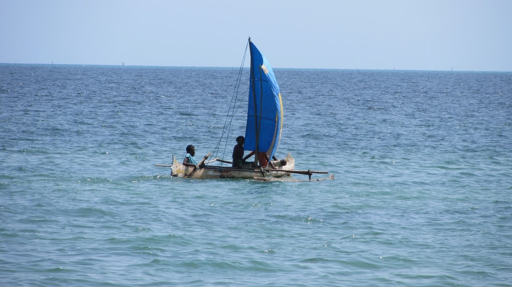 two people in boat on blue body of water during daytime