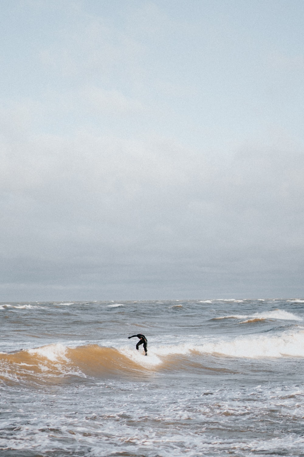 person surfing on sea wave under white sky