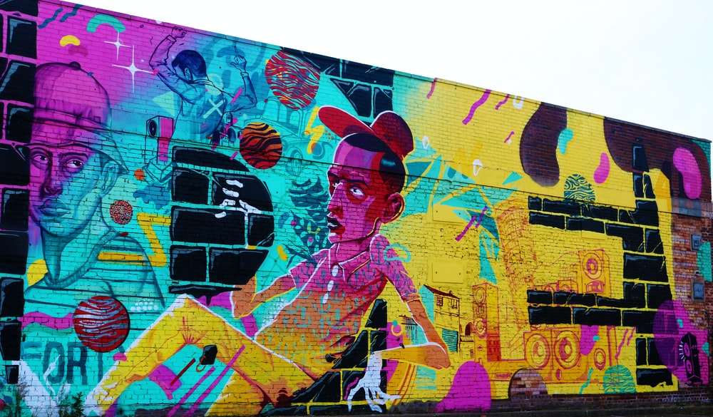multicolored man sitting themed graffiti art