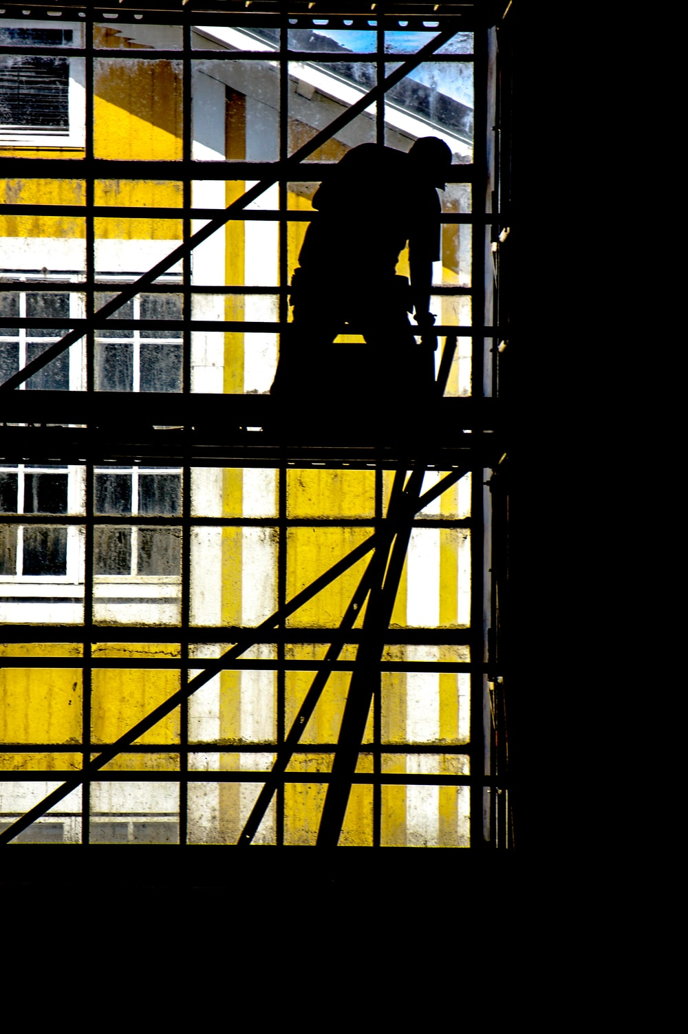 silhouette of man standing on the scaffolding