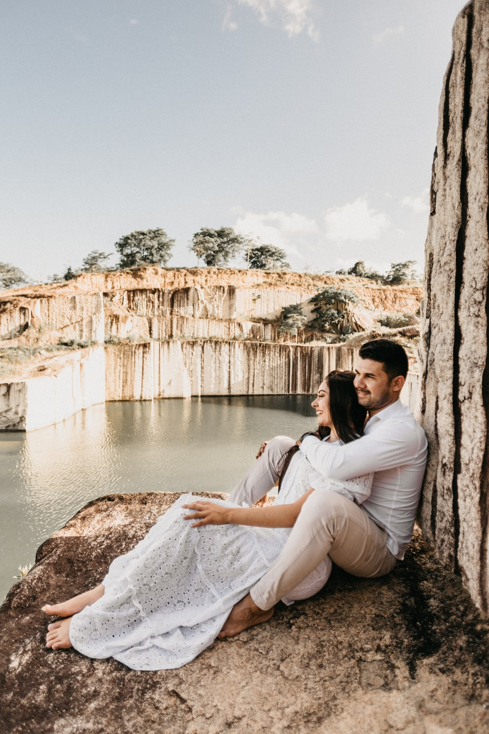 smiling man and woman sitting on rock near body of water during daytime