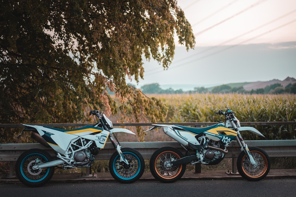 two motocross dirt bike parked near fence during near tree