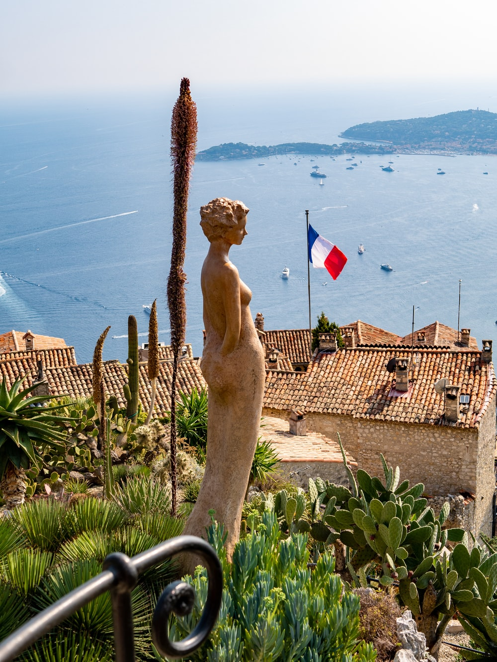 woman brown statue with view of France flag during daytime