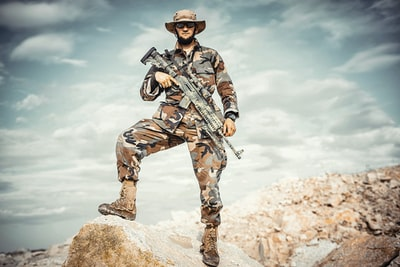 man wearing brown and green camouflage uniform holding rifle while standing on rock army zoom background