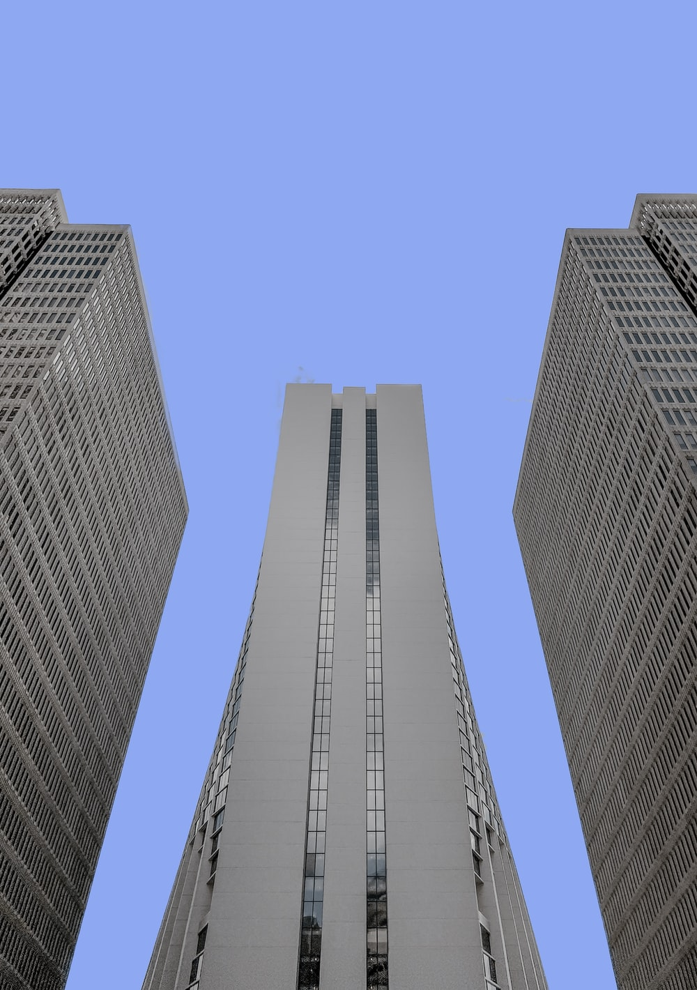 low-angle photo of white high-rise building under blue sky