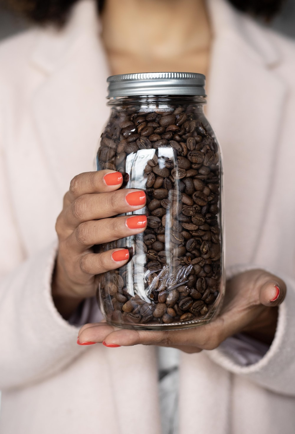 person holding clear glass jar with coffee beans