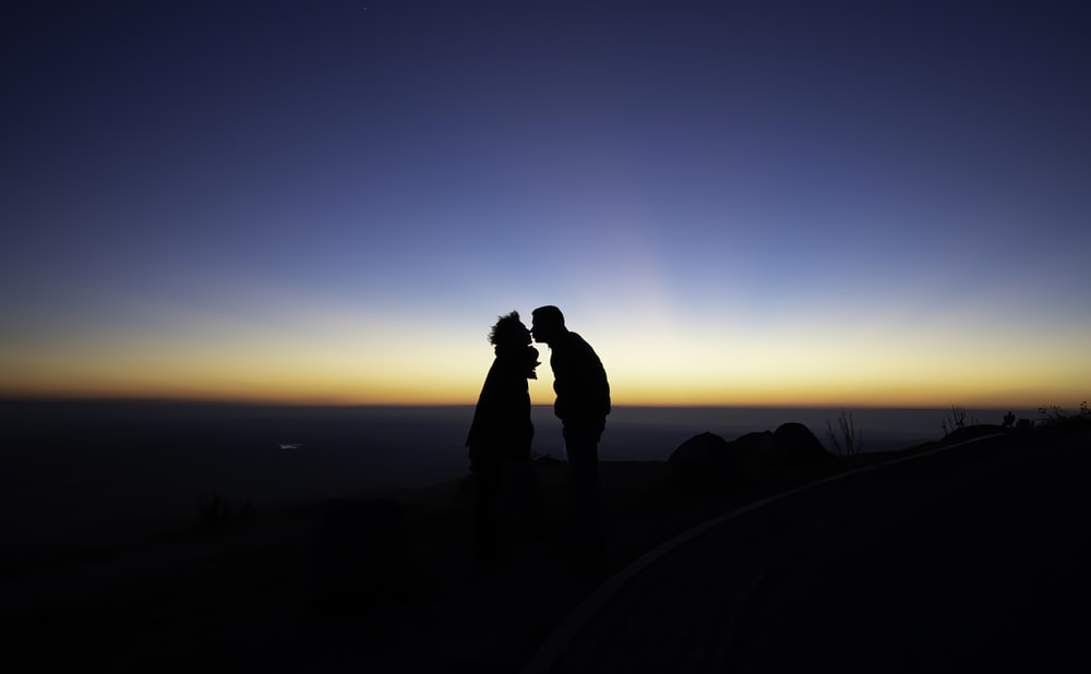 silhouette of two person standing while facing each other and kissing on lips