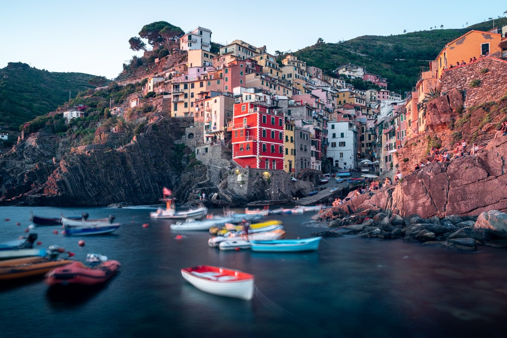 assorted-colored boats on body of water viewing Manarola village in Italy during daytime