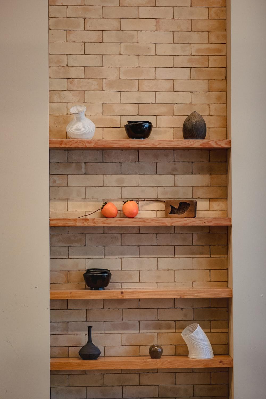 white and black vases on wooden floating shelf
