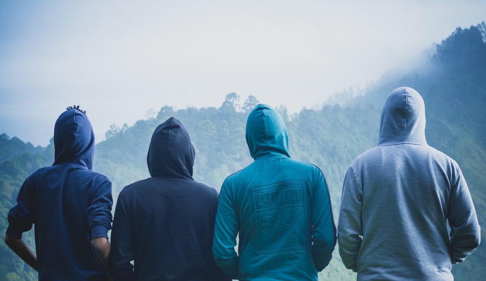 four person wearing pullover hoodies