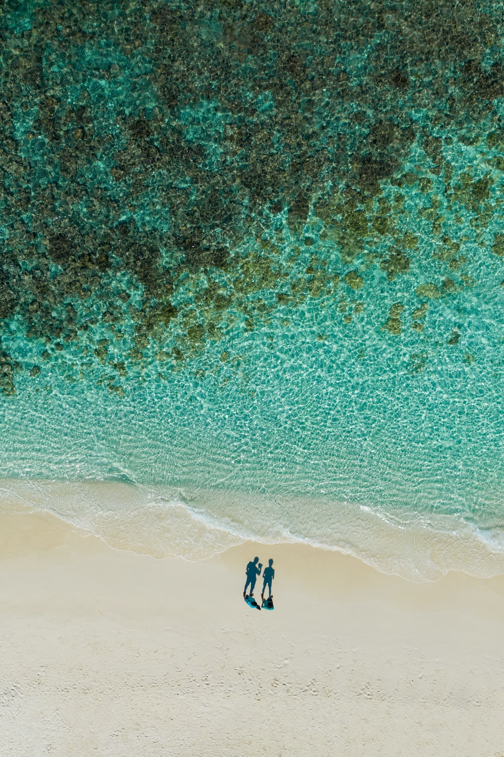 aerial photography of two people standing near seashore during daytime