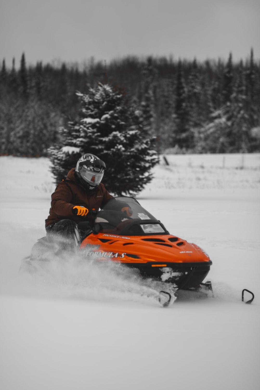 man riding snow mobile during daytime