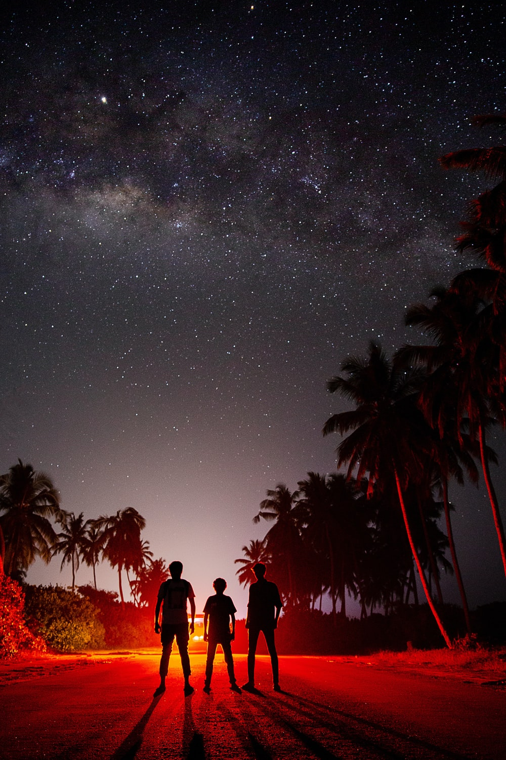silhouette of three people standing during night time