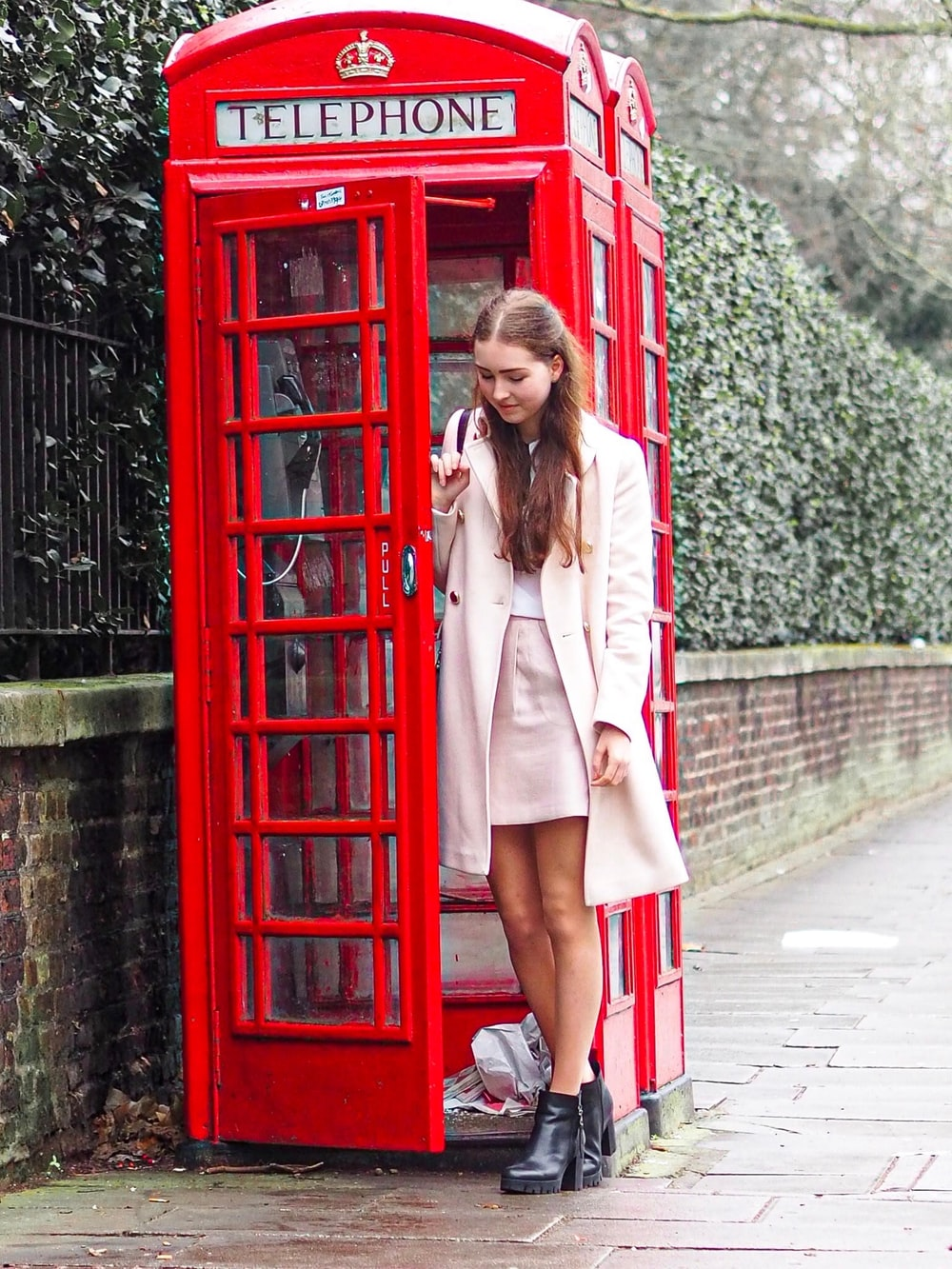 woman standing near the red telephone booth