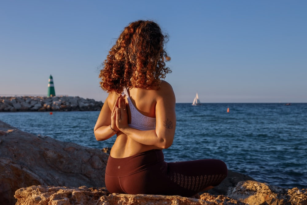 woman sitting while doing yoga on rock viewing body of water during daytime