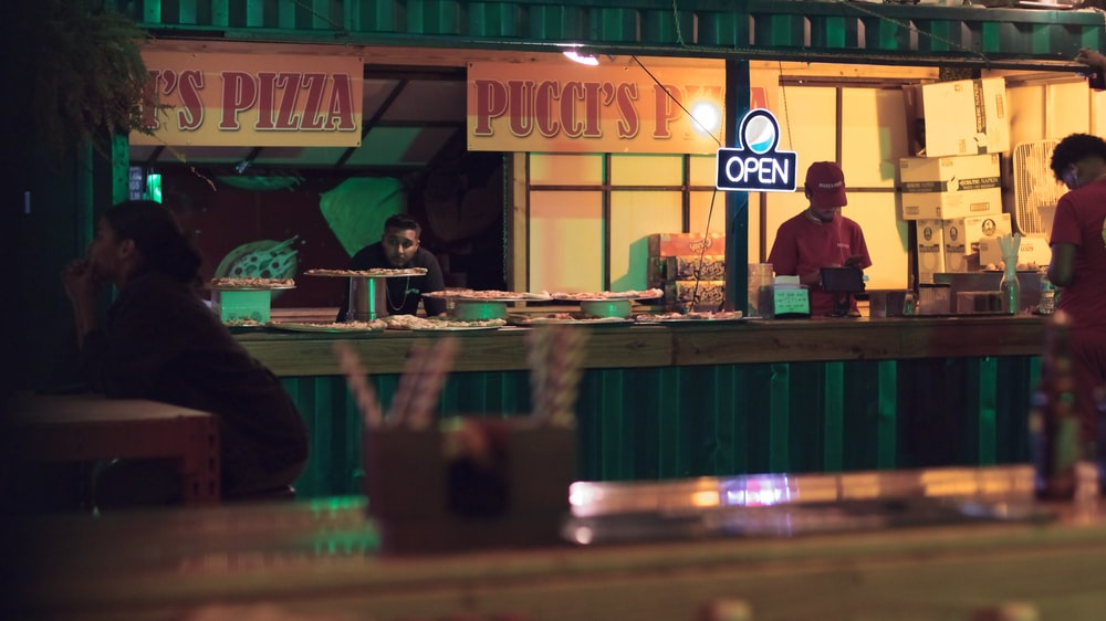 man standing near the pizza stall