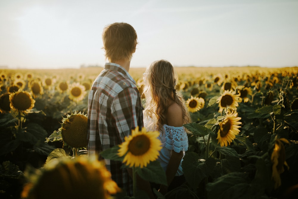 man and woman standing near sunflower field during daytime